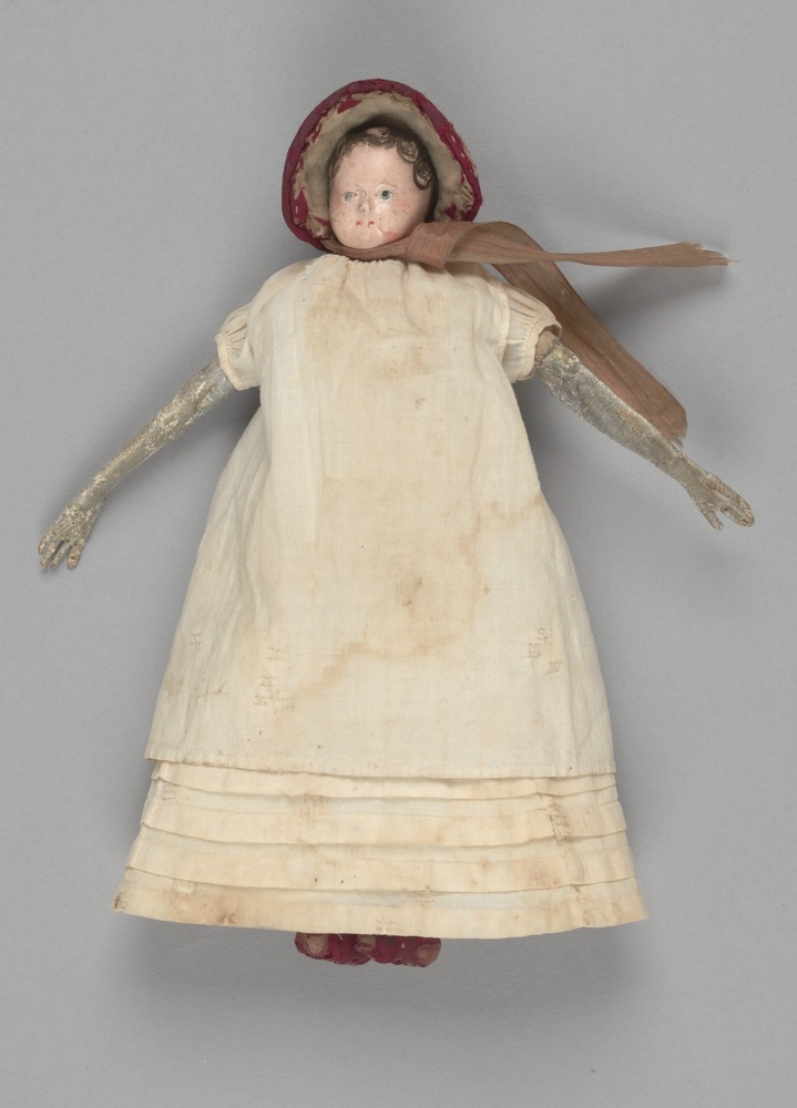 Picture of Elizabeth Batman's old doll wearing red bonnet and plain off-white dress