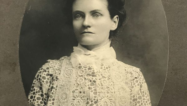 Portrait of a woman with hair up wearing a lacy blouse