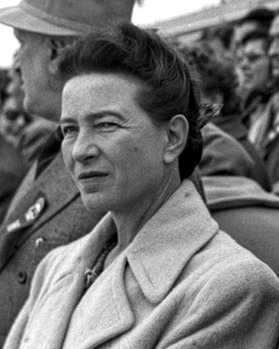 Simone de Beauvoir squints towards the camera. She stands in a crowd in Beijing.