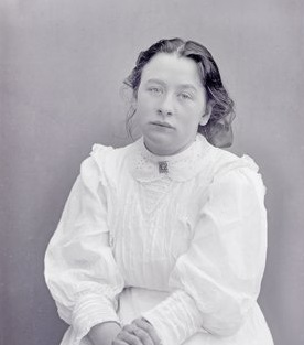 A portrait of Adela Pankhurst, seated, facing the camera, dressed in white with her hair loosely pulled back.