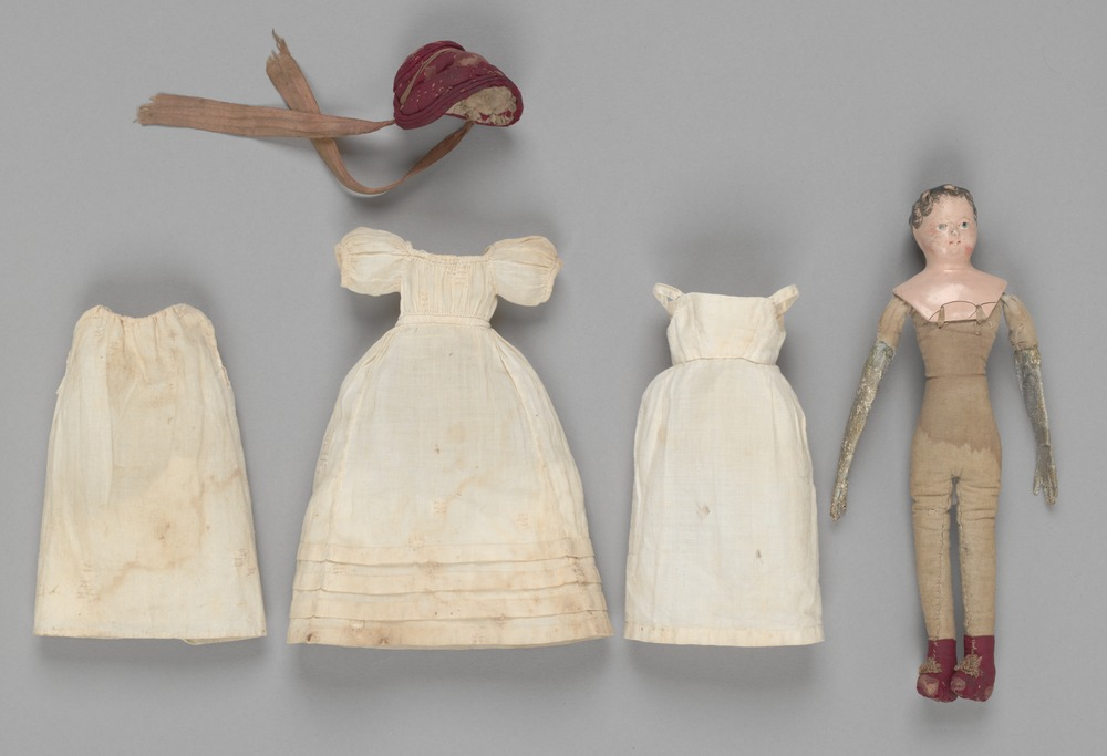 Items of clothing worn by Elizabeth Batman's doll, including petticoat, pinafore, dress and sun bonnet. Also picture of doll without clothing