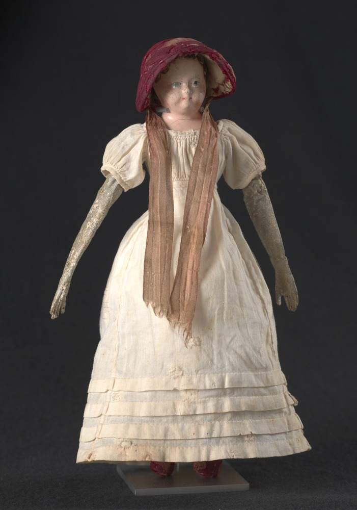 Elizabeth Batman's doll wearing red sun bonnet and cream dress