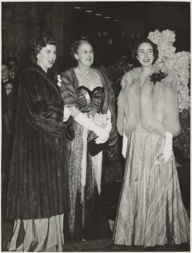 Three women wearing evening gowns standing together having their photograph taken