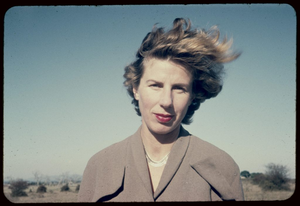 Woman with red lipstick and brown coat facing the camera