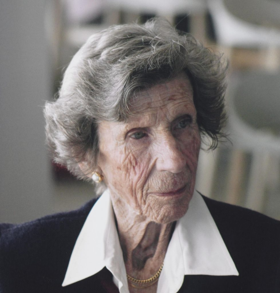 Older woman with cropped grey hair and white collared shirt