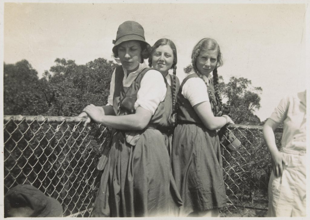 Three teenaged girls in school uniform standing in front of a wire fence