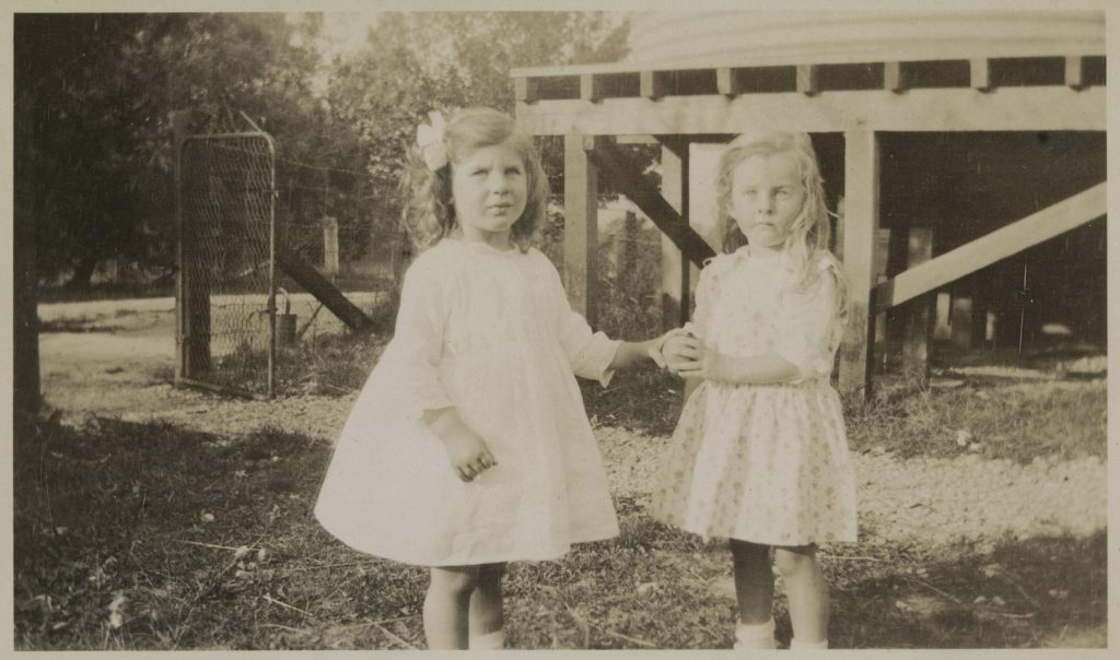 Two little girls in dresses holding hands
