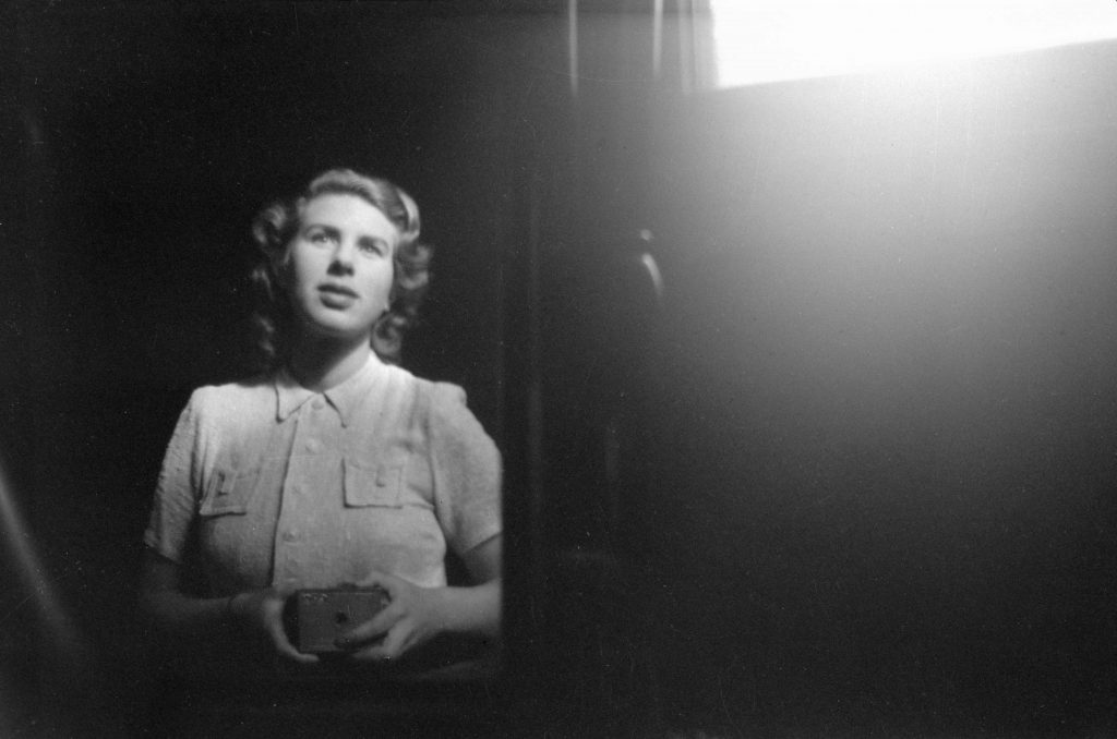 Young woman taking a self-portrait in mirror