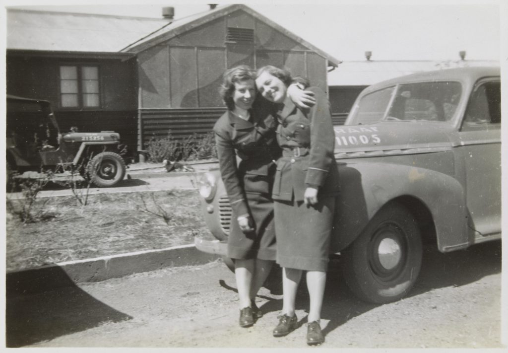 Two young women in Air Force uniform smiling and standing in front of a car