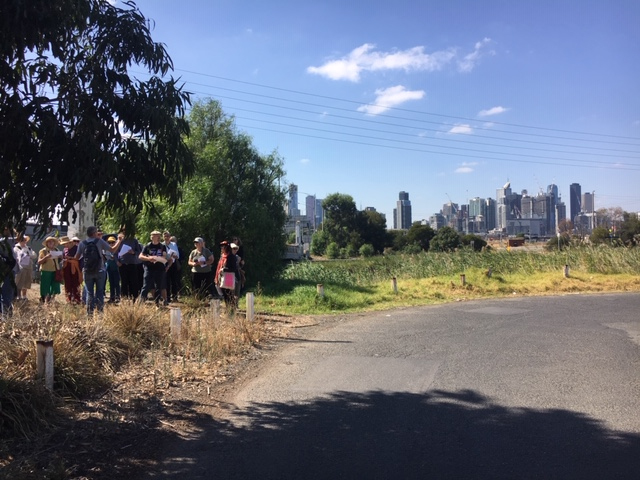 walking tour group listening to presenter with melbourne city skyline in background