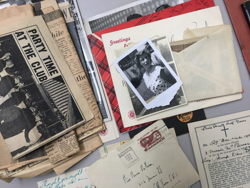 Piles of mixed materials including letters, photographs and newspaper clippings