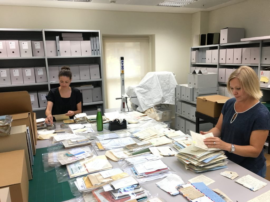 Two women sitting at benches sorting papers into piles