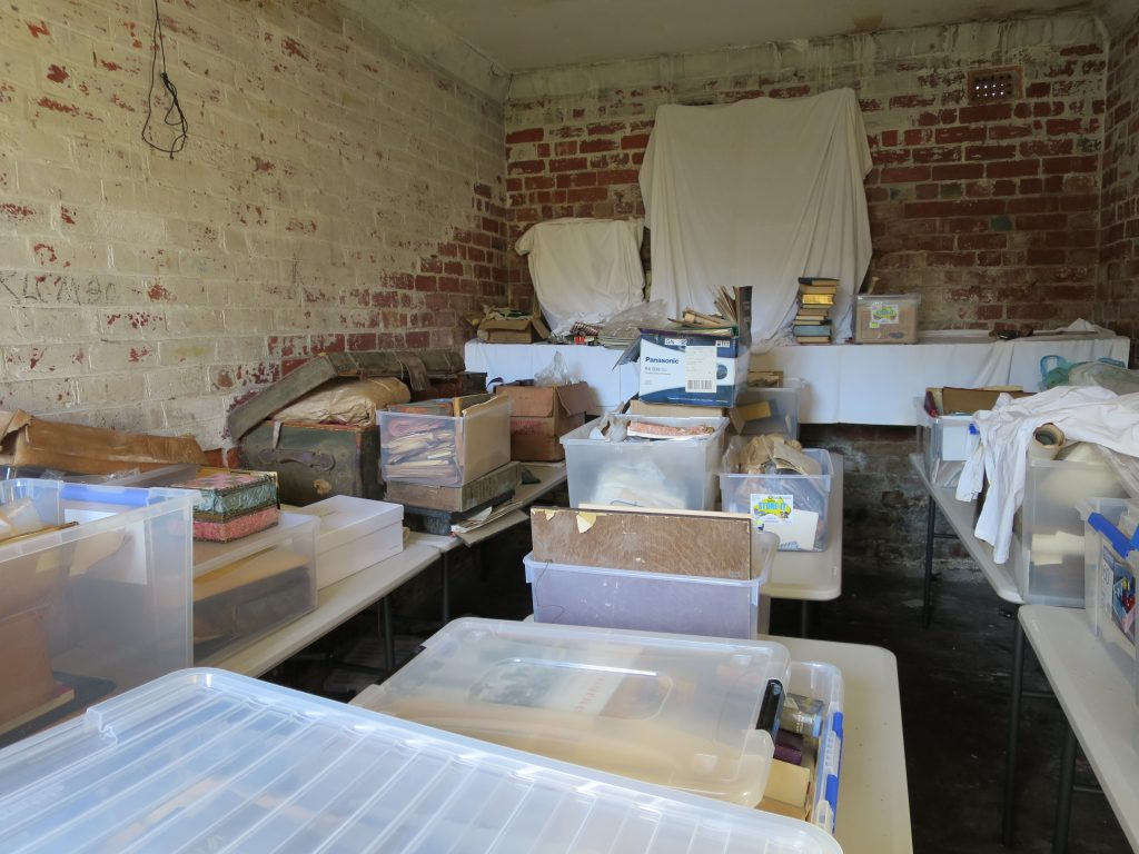 Internal view of a brick-walled storage area containing a large number of boxes and plastic tubs of papers
