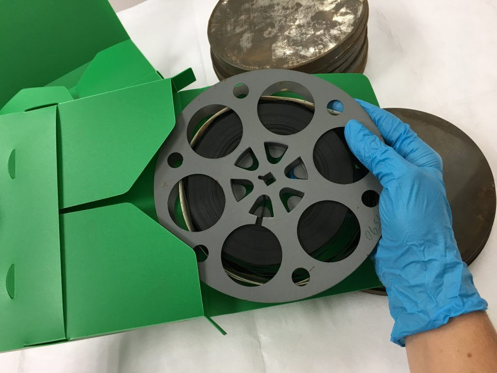 Blue-gloved hand placing 16mm film reel into green polypropylene enclosure