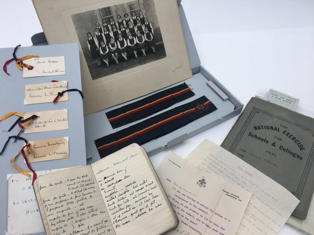Papers, photographs and ribbons from schooling arranged for viewing