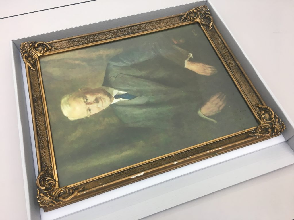 Framed portrait painting of a man in an archival board box
