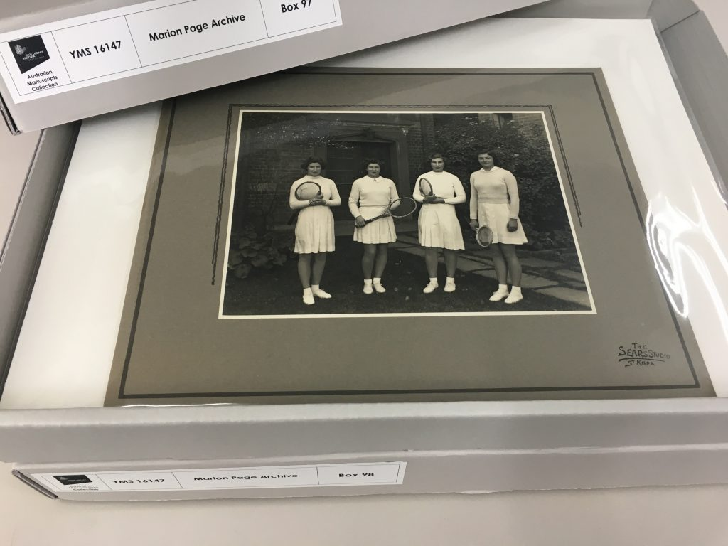 Mounted black and white photograph of four young women in tennis outfilts placed in archival sleeve and box