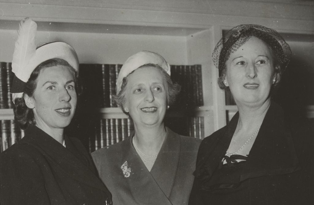 Three women with hats facing slightly away from the camera