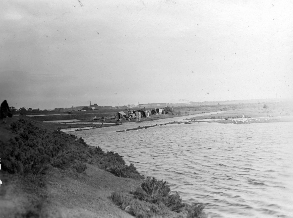 View across hillside and stretch of water to a group of shanties. Industrial landscape in the background.