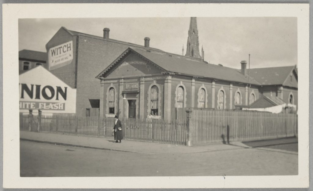 Black and white photograph of old building at corner of Exhibition and Little Lonsdale Streets