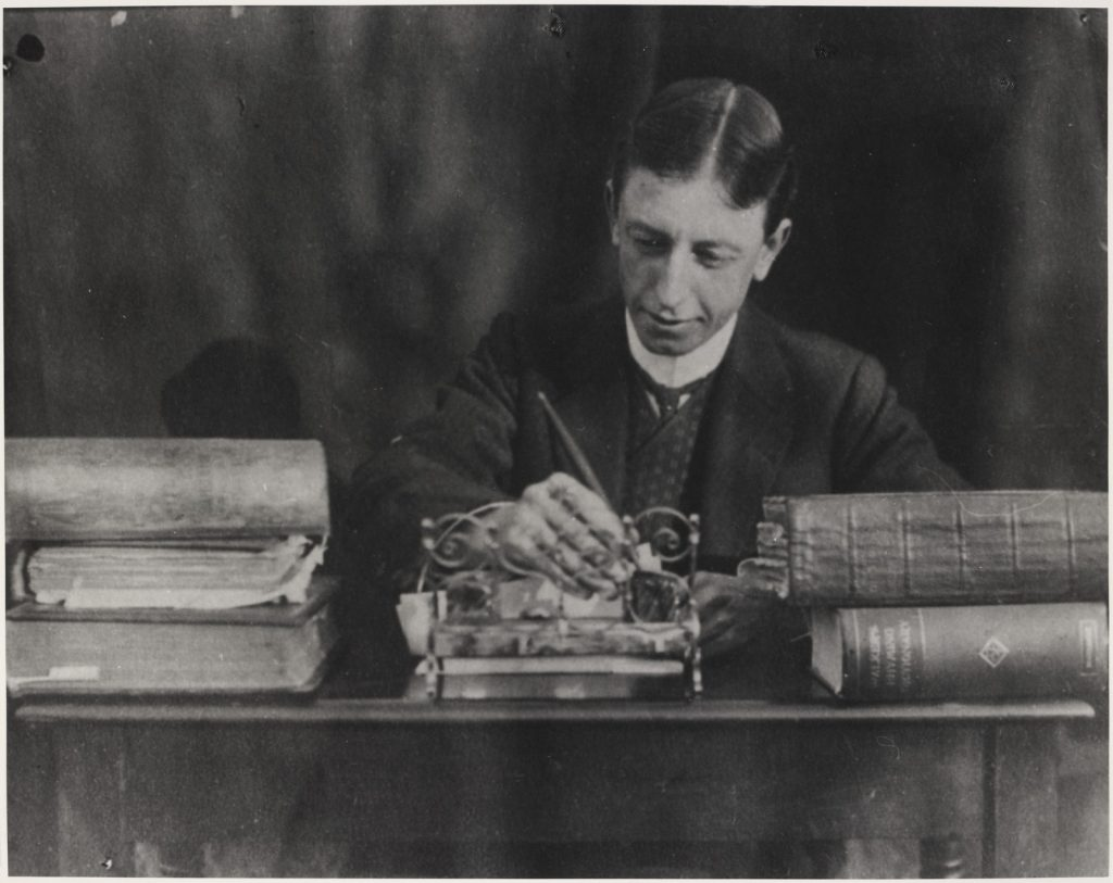 Black and white photograph of poet C.J.Dennis sitting at his writing desk with a pen poised in hand and books stacked up around him.