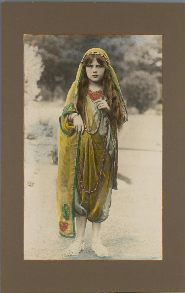 Black and white photograph with hand colouring of  a young girl dressed in costume