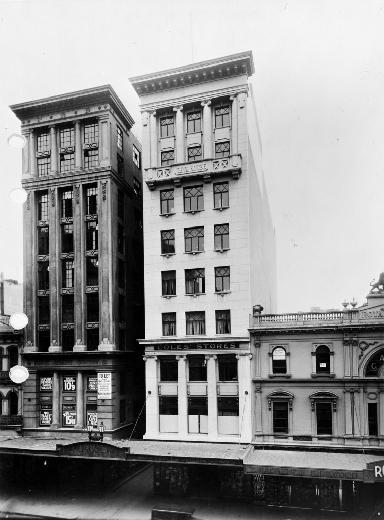 "Black and white photo of several buildings in Bourke Street, including a double-story brick building with sign on exterior reading ""T MacKenzie Kirkwood"""