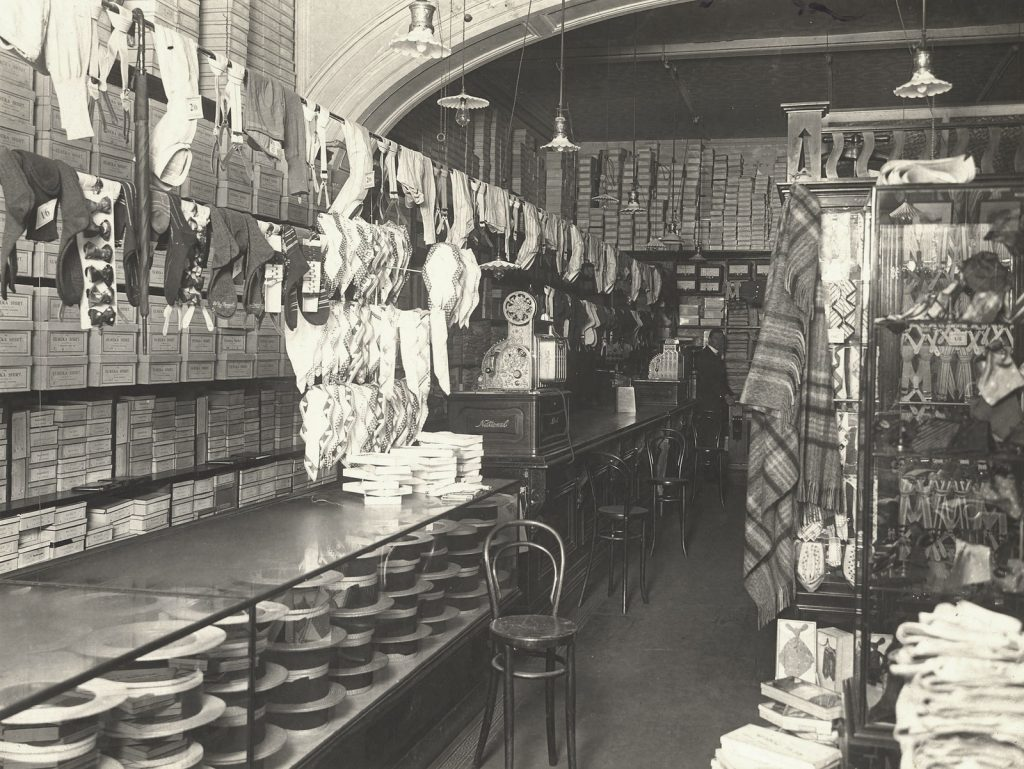 Black and white photo of interior of T. Kirkwood MacKenzie's store. Merchandise is on display and Kirkwood MacKenzie is visible at the back of the shop