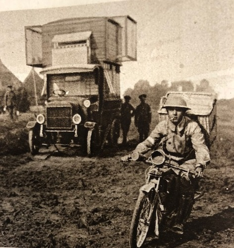 A motor cyclist rides away from army lorry with a basket of pigeons on his back