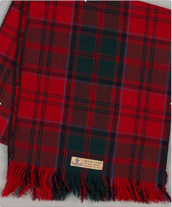 "Photograph of tartan scarf with label on it reading ""T. MacKenzie Kirkwood"""