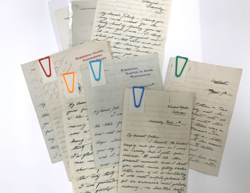 Series of handwritten letters displayed in an array, held together with archival plastic paperclips