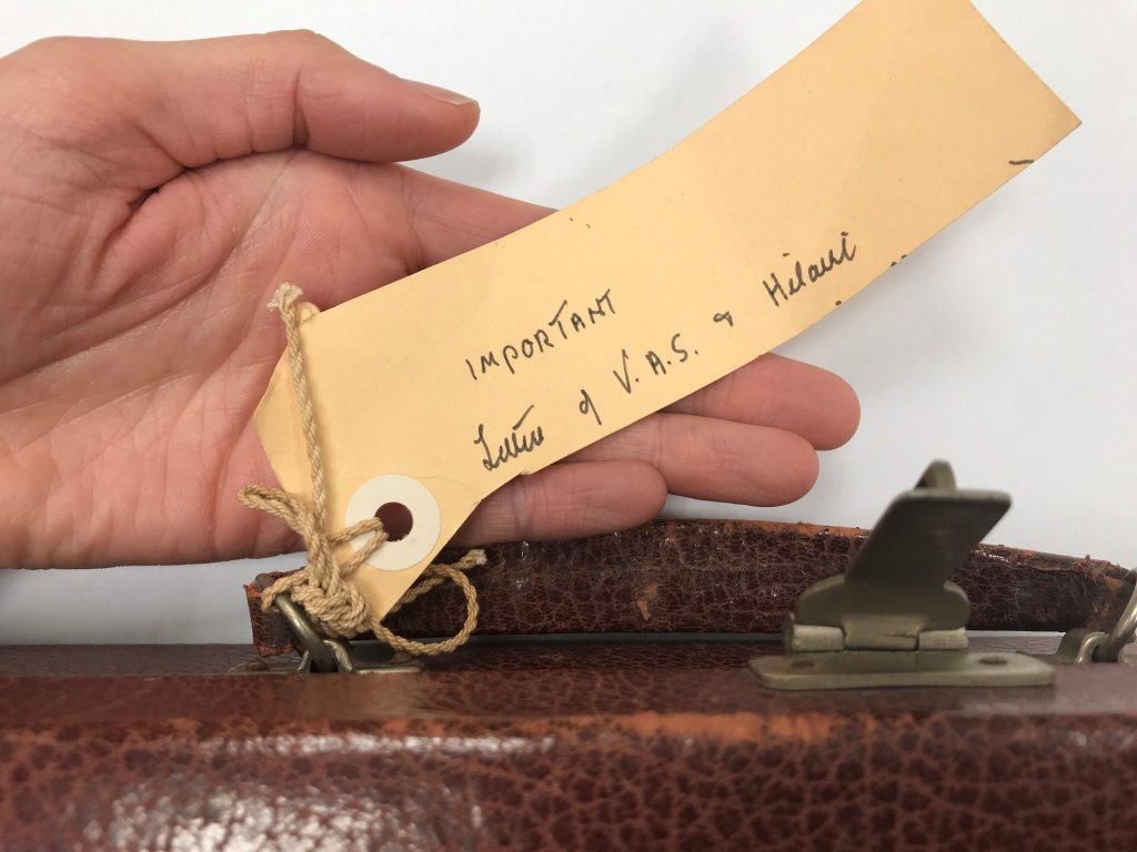 Yellow label with handwritten text tied by string to the handle of a small writing box