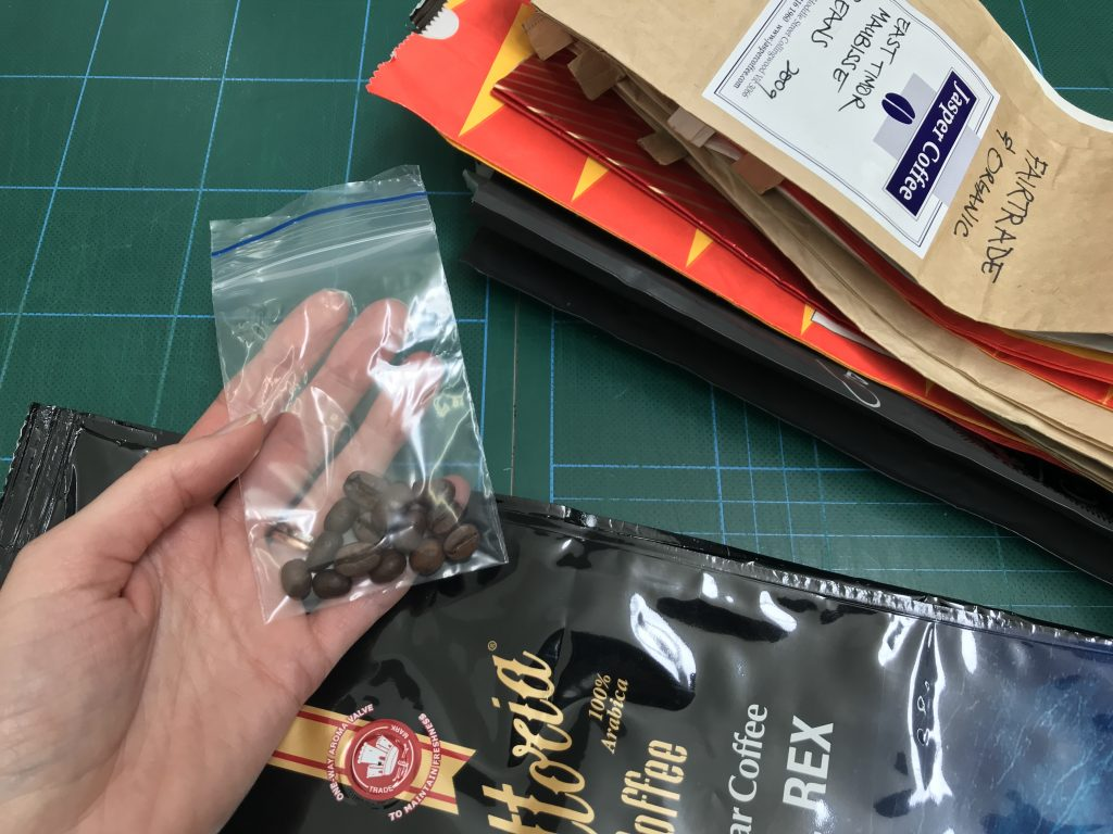 Colour photograph of close up of a pile of empty coffee bags, and a hand holding a plastic zip lock bag containing loose coffee beans.