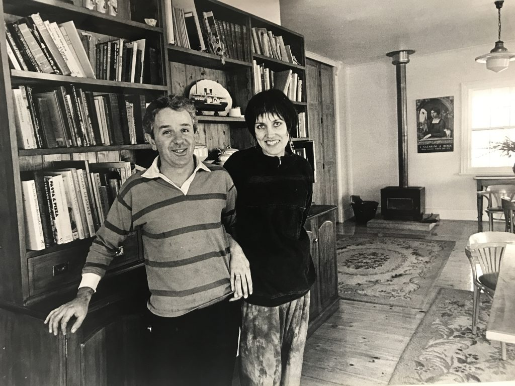 A black and white photograph of a man and woman smiling and looking directly at the camera, as they lean against a large bookshelf.
