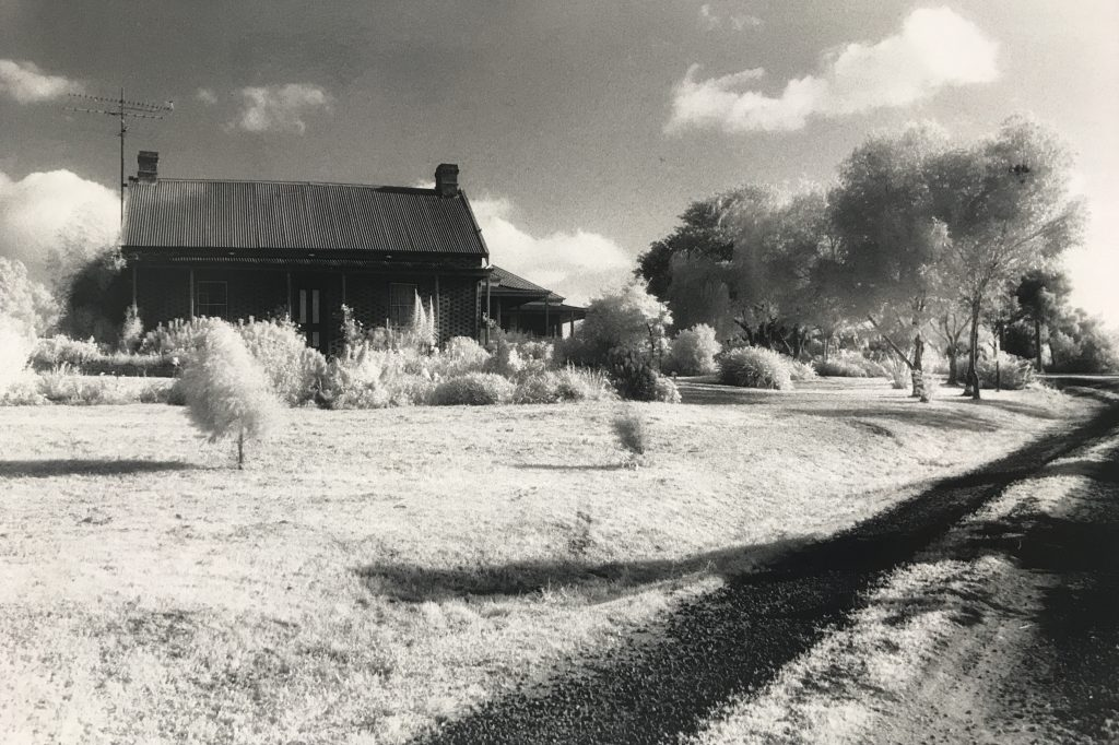Black and white photograph featuring a house in the background set against a sky with white clouds, while an open stretch of grass with trees surrounds the house in the foreground.