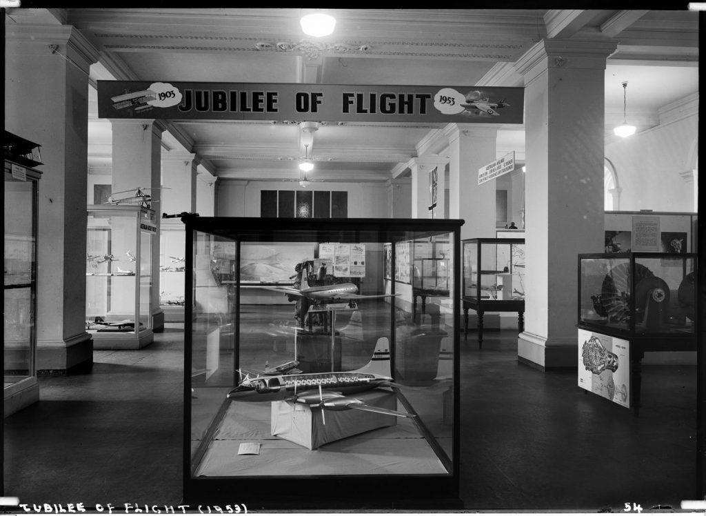 Black and white photo of model aeroplanes in glass cases with banner overhead reading 'Jubilee of Flight'.