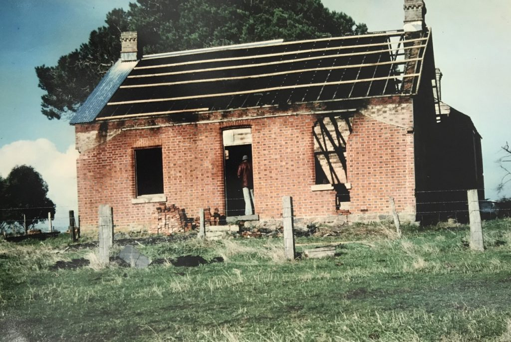Colour photograph of an old red brick house structure, damaged by fire; the roof is visibly gutted.