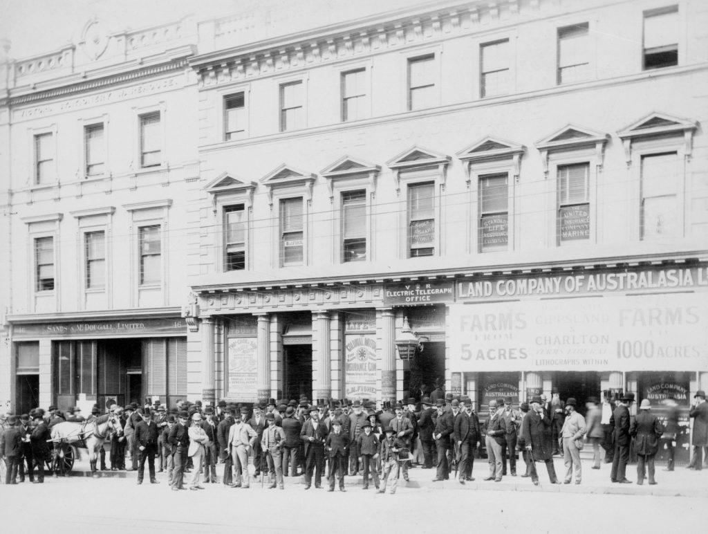 Black and white photo of large crowd of men standing outside Sands & McDougall building