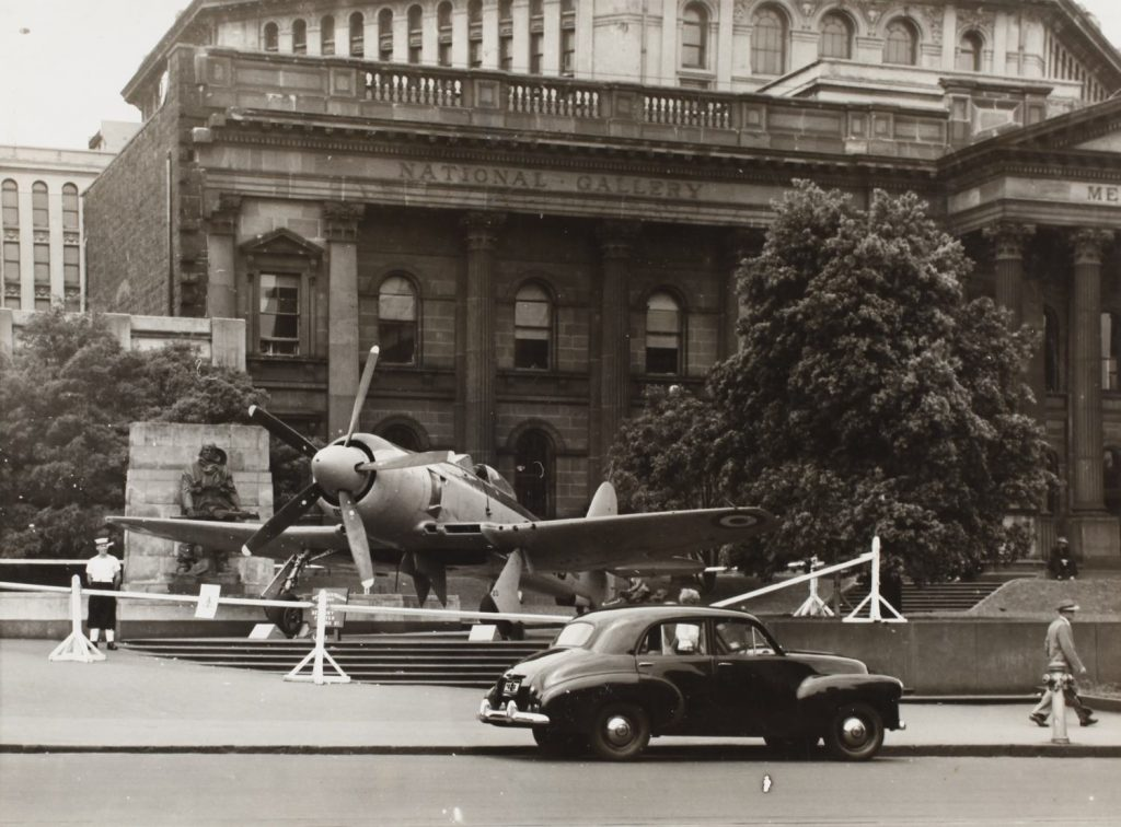 Black and white photo of Sea Fury military aircraft on steps outside the library