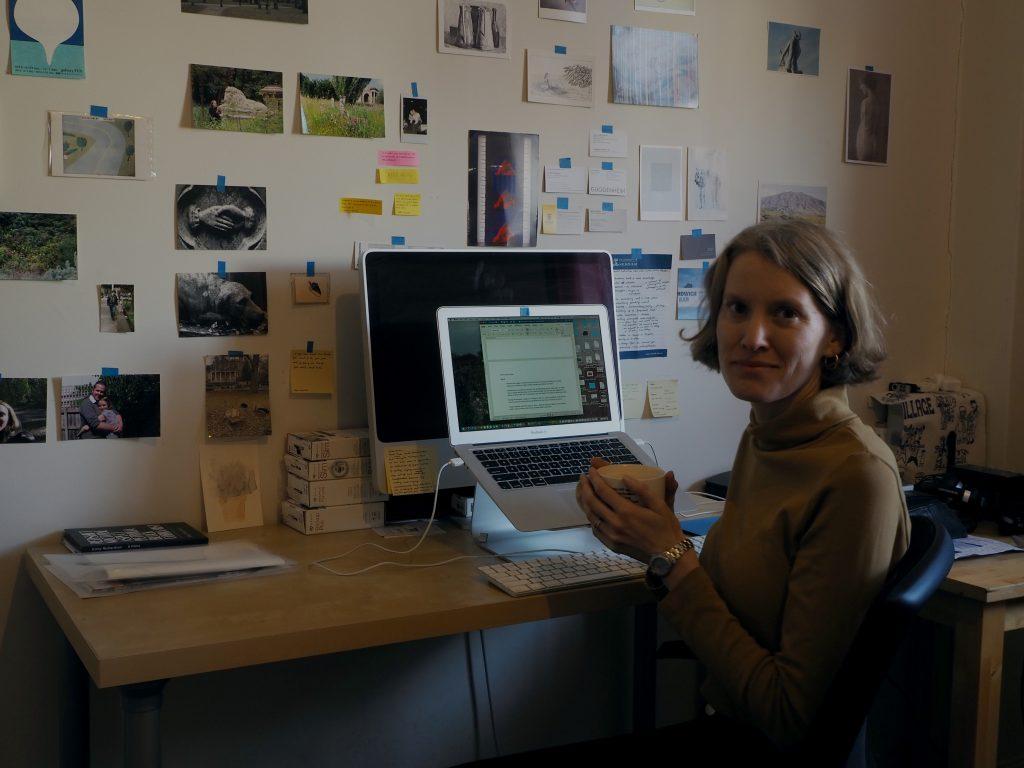 Woman sitting at a desk facing the camera