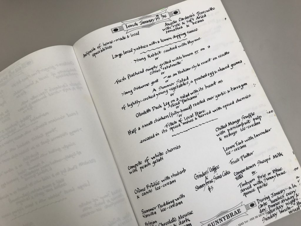 Colour photograph of a book, laying open, depicting black handwritten text.