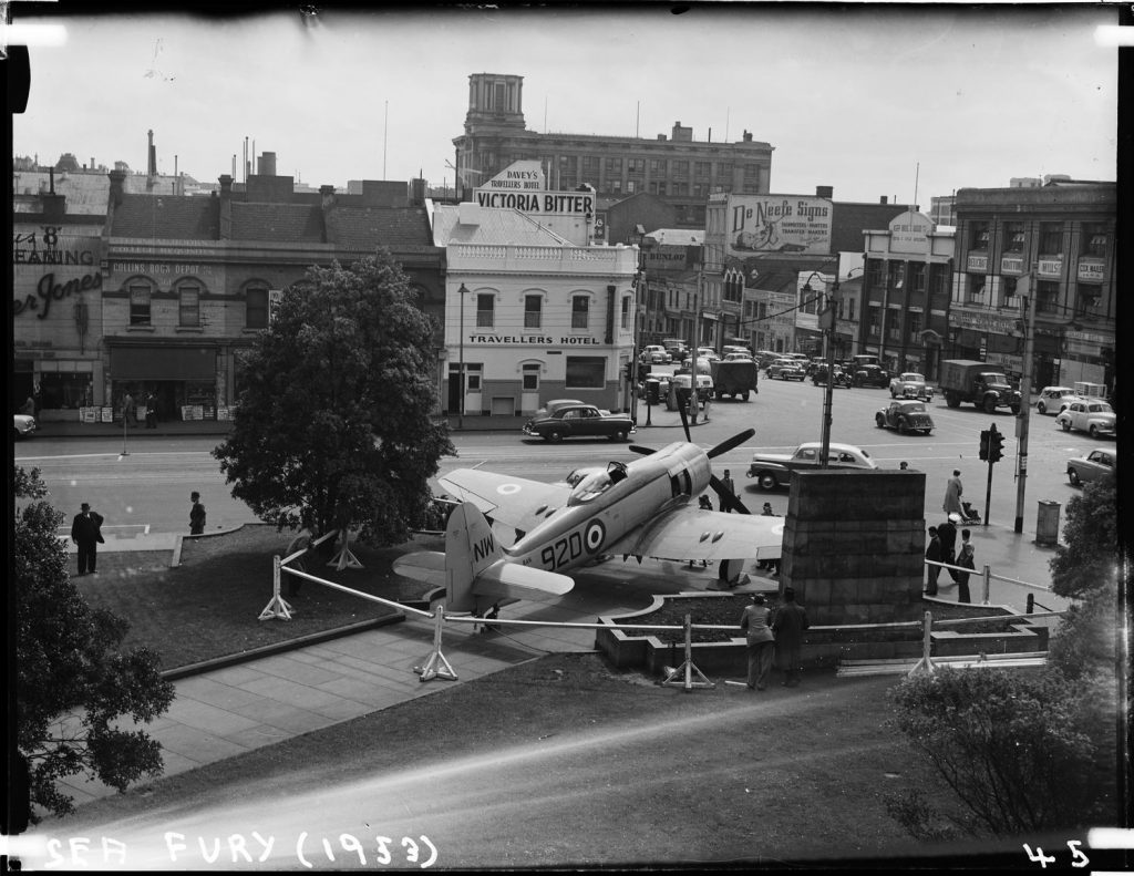Black and white photo of Sea Fury outside Library, hotels and shopfronts of Swanston Street in background