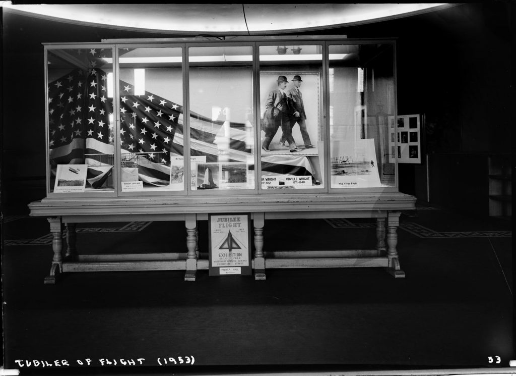 Black and white photo of exhibition display case featuring American flag and picture of the Wright brothers