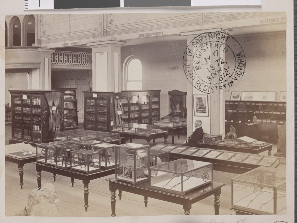 Black and white photo showing glass cabinets and rows of glass cases in science museum. Attendant sits in middle of room