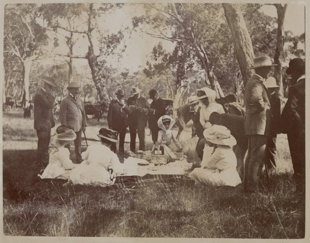 Ladies in white dresses and hats since on picnic rug in bush, men in suits and hats stand around in background