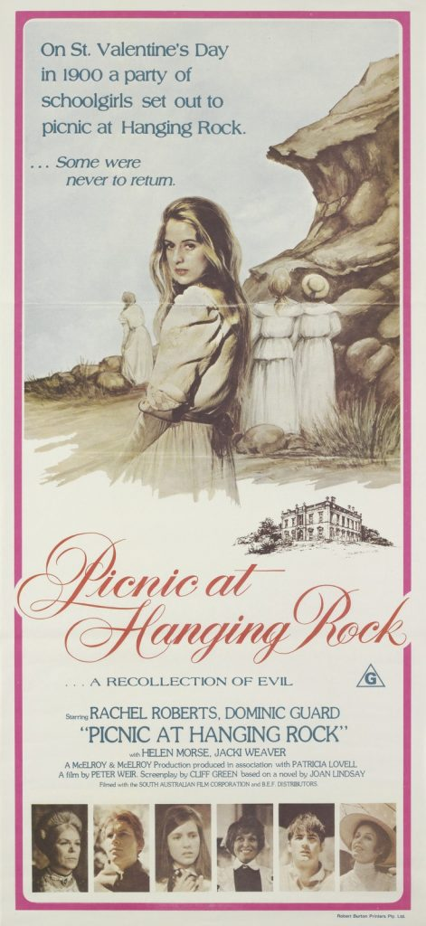 Colour poster advertising 'Picnic at Hanging Rock' film, features young lady in white standing in front of rocks, looking over her shoulder towards camera. Several other young ladies are in background, also wearing white. Cursive writing underneath reads 'Picnic at Hanging Rock'. Photos of main cast members along bottom of poster