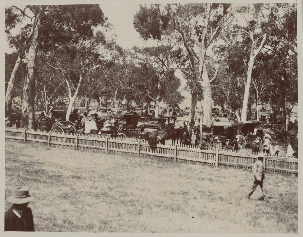 Black and white photo of crowd behind fence at Hanging Rock Races on New Year's Day in 1910