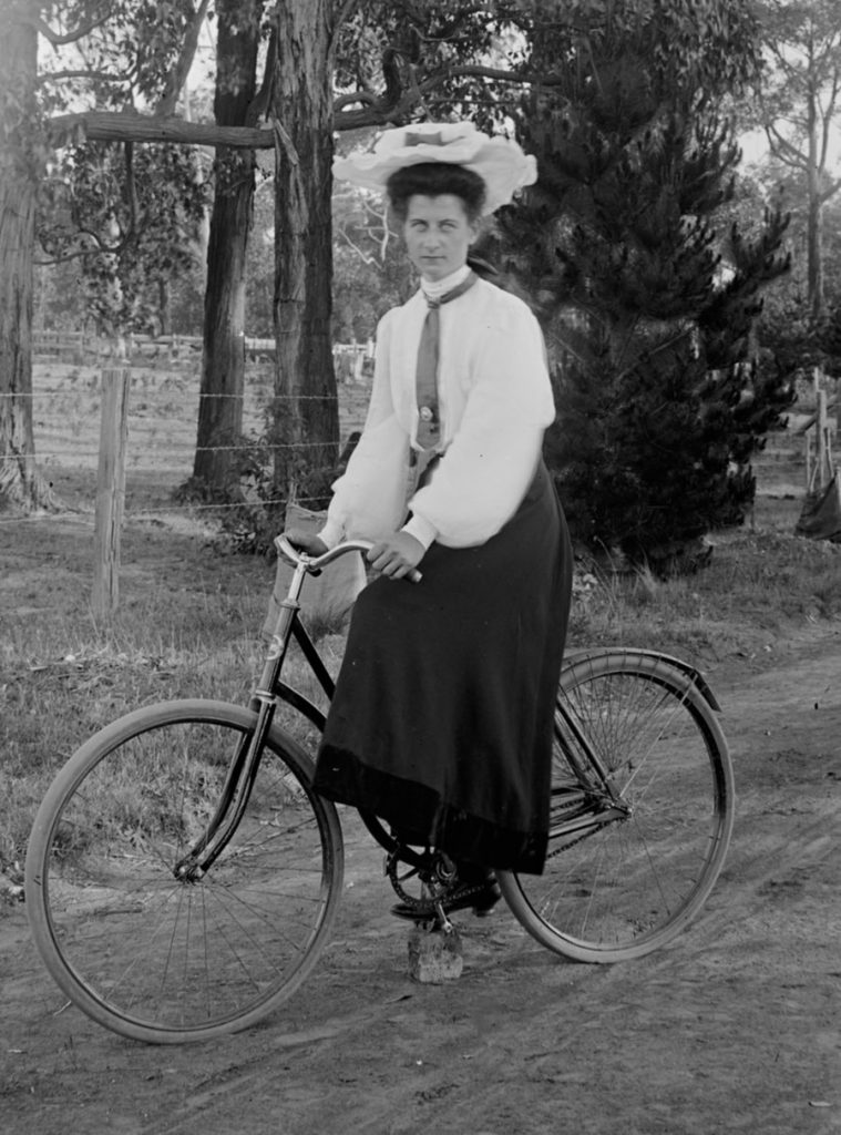 Black and white photo of a middle- aged woman sitting on a bicycle in a very long skirt