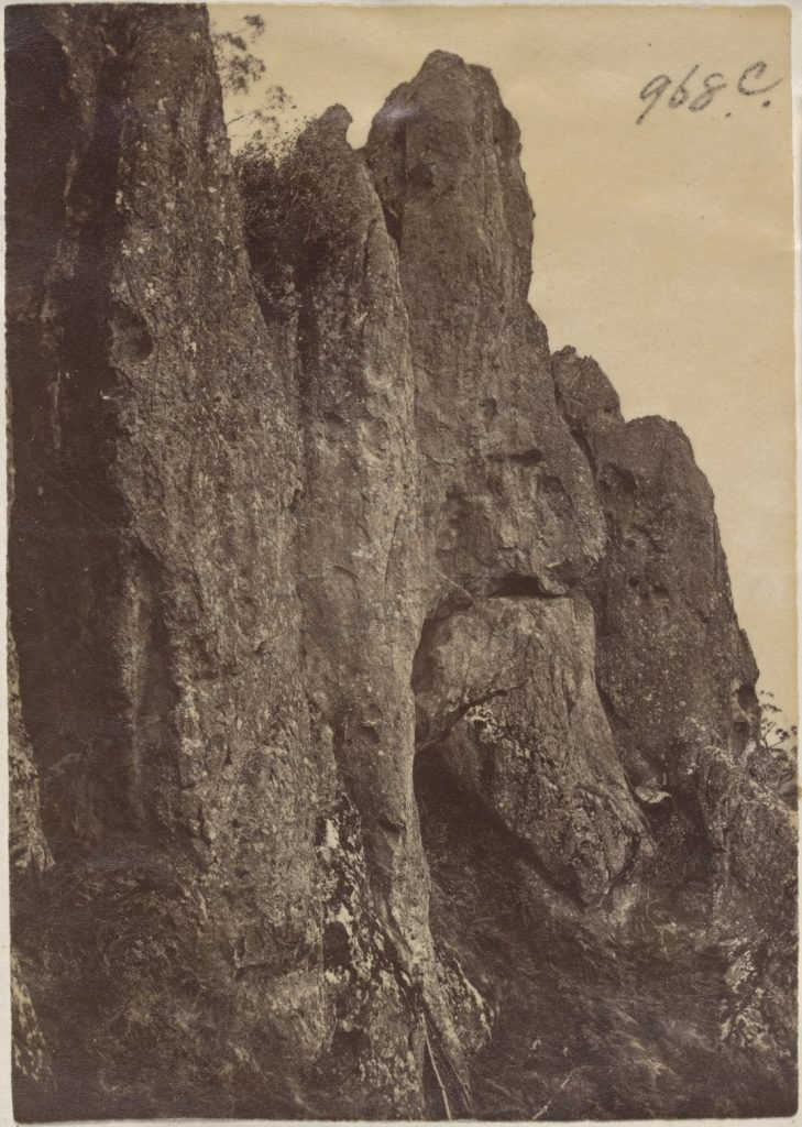 A sepia photograph of a large rock formation.