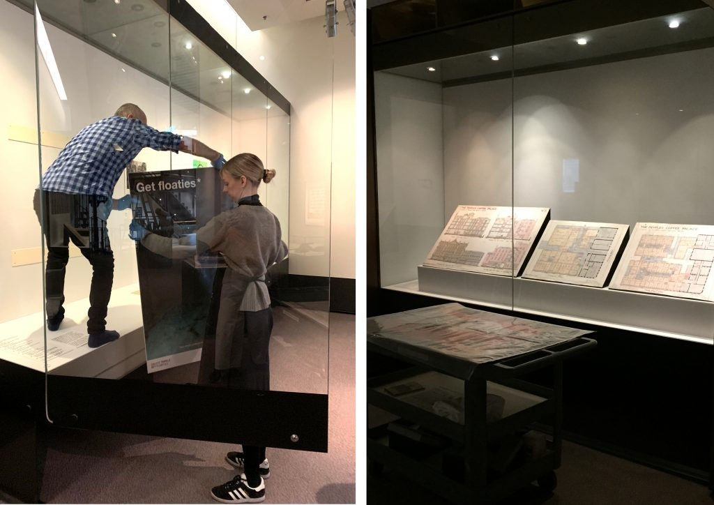 Two images: (left) man and woman lifting a poster into a showcase during installation; (right) three architectural drawings installed in a showcase